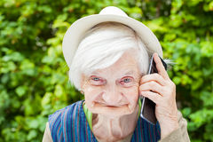 Happy smiling grandmother talking on mobile phone. Picture of a happy smiling grandmother talking on a mobile phone outdoor in the garden Royalty Free Stock Photography