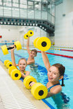 Happy and smiling group of children doing exercises in a swimming pool Royalty Free Stock Images