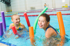 Happy and smiling group of children learning to swim with pool noodle Royalty Free Stock Photos