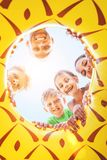 Happy smiling group of childs, teens and adult people look down. Into the inflatable ring hole royalty free stock images