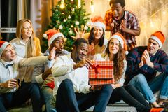Happy smiling friends opening magic Christmas gift. Happy smiling group of friends opening magic Christmas gift Royalty Free Stock Photo