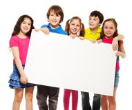 Kids showing blank placard. Happy smiling group of kids, friends, boys and girls, showing blank placard board to write it on your own text isolated on white Royalty Free Stock Photo