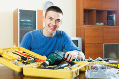 Happy smiling guy organizes tools on table Royalty Free Stock Photos