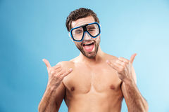 Happy smiling guy in swimming goggles showing thumbs up gesture royalty free stock image