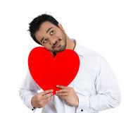 Happy smiling handsome man holding large red heart to chest, daydreaming Royalty Free Stock Photo