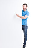 Happy smiling handsome points finger on blank banner. Royalty Free Stock Photos