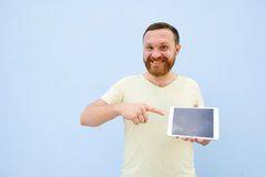 Happy smiling Handsome young man with a beard showing something on a tablet  on a blue background, bright and light Royalty Free Stock Photography