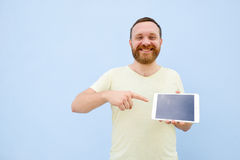 Happy smiling Handsome young man with a beard showing something on a tablet  on a blue background, bright and light Stock Photos
