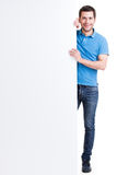 Happy smiling handsome young man look out from blank banner. Happy smiling handsome young man look out from blank banner - isolated on white Royalty Free Stock Photography