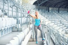 Happy, smiling healthy girl working out and training while taking selfies Stock Photo