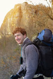 Happy smiling hiker man with backpack is resting in the autumn m Stock Photography