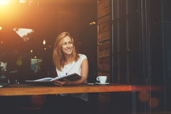 Happy smiling hipster girl enjoying good day while relaxing in cozy cafe bar after work day. Young beautiful cheerful female looking away while sitting with Stock Photography