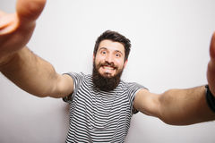 Happy smiling hipster man with beard  taking selfie with hands on camera. Stock Images