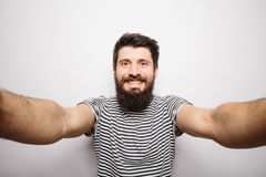 Happy smiling hipster man with beard taking selfie with hands on camera. Royalty Free Stock Photography