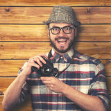 Happy smiling hipster with retro camera in hands Royalty Free Stock Images