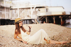 Happy smiling hipster woman take a rest lying on a sea beach, casual dress Stock Images