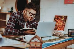 Happy Smiling Illustrator Focused on Work Project. Portrait of Young Bearded Freelance Hipster Wearing Casual Shirt Sits at Workplace Using Laptop. Creative stock photo