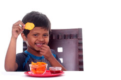 Happy & smiling Indian boy eating unhealthy chips Stock Photos