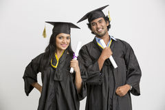 Happy smiling Indian college graduates wearing cap and gown holding diploma Stock Images