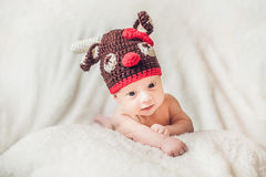 Happy smiling infant baby boy portrait dressed in christmas deer. Crocheted hat, winter holidays concept Royalty Free Stock Image