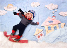 Happy smiling infant baby boy skier. Skiing in snow mountains, wearing scarf and warm hat. Textile decoration of a winter city Royalty Free Stock Photo