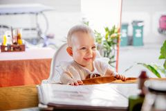 Happy smiling Infant girl is sitting on a baby  high chair in a street cafe. Children reading the menu in the restaurant. Happy smiling Infant girl is sitting on royalty free stock photo