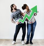Happy smiling interracial couple holding a growth arrow royalty free stock image