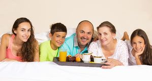 Happy smiling joyful family having breakfast in bed. Group portrait looking happy smiling joyful family, mother, father, daughters, son having breakfast in bed Royalty Free Stock Images