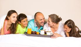 Happy smiling joyful family having breakfast in bed. Group portrait looking happy smiling joyful family, mother, father, daughters, son having breakfast in bed Royalty Free Stock Image
