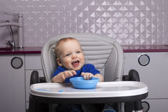 Happy smiling kid in a baby chair Royalty Free Stock Image