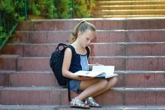 Schoolgirl 8 years old doing homework on stairs reads book. royalty free stock photos