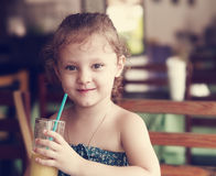Happy smiling kid girl drinking fresh juice from glass in cafe. Stock Photo