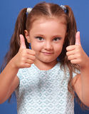 Happy smiling kid girl showing two hands thumb up on blue backgr Royalty Free Stock Image