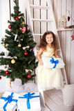 Happy smiling kid holding gifts near Christmas tree. Royalty Free Stock Photography