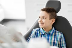 Happy smiling kid patient at dental clinic. Medicine, dentistry and healthcare concept - happy smiling kid patient at dental clinic Stock Image