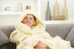 Happy smiling kid sitting in bathrobe at home sofa Stock Photo