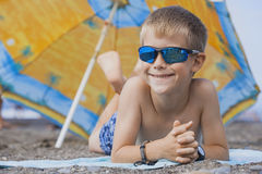 Happy smiling kid is sunbathing on a beach Stock Photography