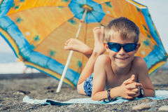 Happy smiling kid is sunbathing on a beach Stock Image