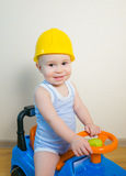 Happy smiling kid in yellow helmet driving a toy car.  Stock Photo