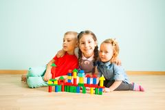Happy smiling kids behind the wooden blocks castle royalty free stock photo