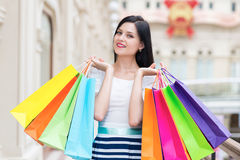 A happy smiling lady with a lot of colourful shopping bags from the fancy shops. Royalty Free Stock Photography