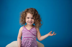 Happy Smiling Laughing Child: Girl with Curly Hair. Happy smiling laughing child looking at camera: girl with curly hair pointing at something or holding royalty free stock images