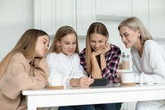Happy smiling lesbian family in casual clothes, two daughters and their mom`s sitting together at the table in the royalty free stock photo
