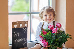 Happy smiling little boy with blooming pink roses in bunch Stock Images