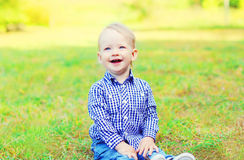 Happy smiling little boy child sitting on grass Stock Photography