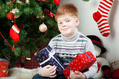 Happy smiling little boy with christmas gift boxes Stock Photos