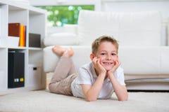 Happy smiling little boy lying on floor Stock Photography