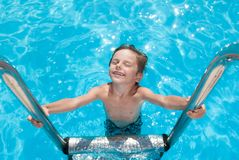 Happy smiling cute little boy standing on chrome stairs in fresh water pool in sunny summer day Stock Images