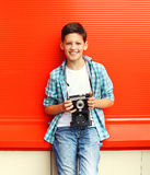 Happy smiling little boy teenager with retro vintage camera. In city over red background Stock Photo
