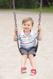 Happy smiling little boy toddler in tshirt and jeans shorts on swing on backyard playground outside Stock Photos